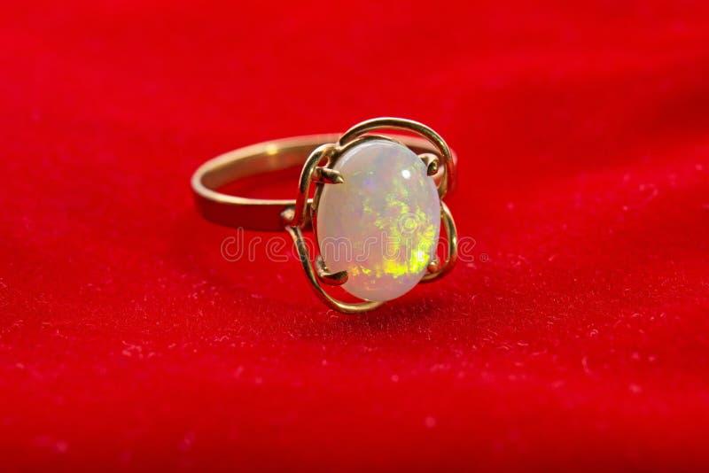 Χρυσό Opal δαχτυλίδι στο κόκκινο βελούδο στοκ εικόνα