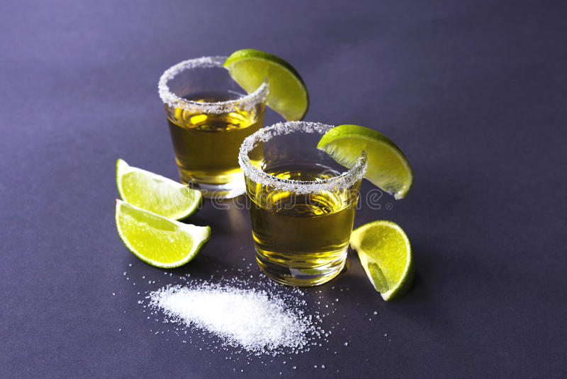 Χρυσό tequila με τον ασβέστη και άλας στο σκοτεινό πίνακα στοκ εικόνες με δικαίωμα ελεύθερης χρήσης
