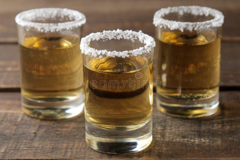 Χρυσό tequila σε ένα γυαλί με το άλας και ασβέστης σε έναν καφετή ξύλινο πίνακα οινοπνευματώδη ποτά στοκ εικόνες