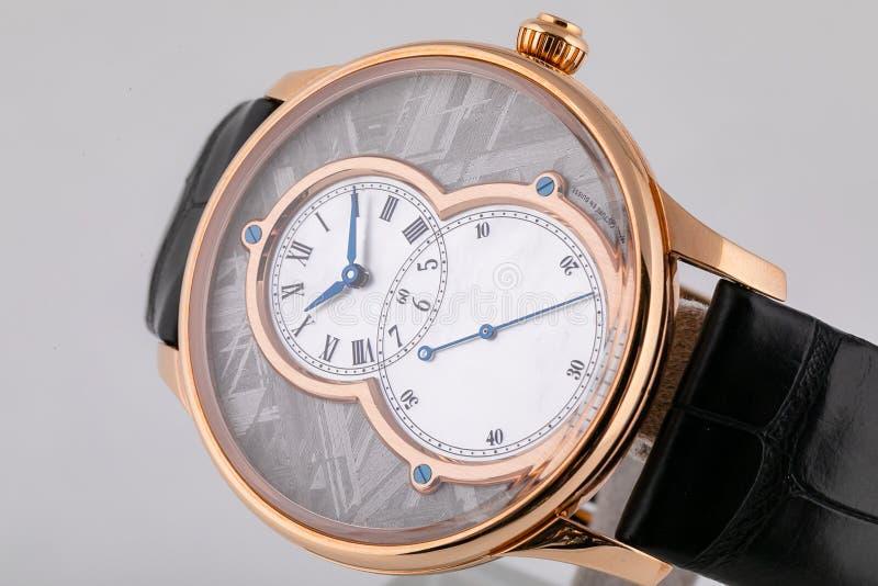 Χρυσό wristwatch με δύο άσπρους πίνακες, μπλε δεξιόστροφα στο μαύρο λουρί δέρματος που απομονώνεται στο άσπρο υπόβαθρο στοκ φωτογραφία με δικαίωμα ελεύθερης χρήσης