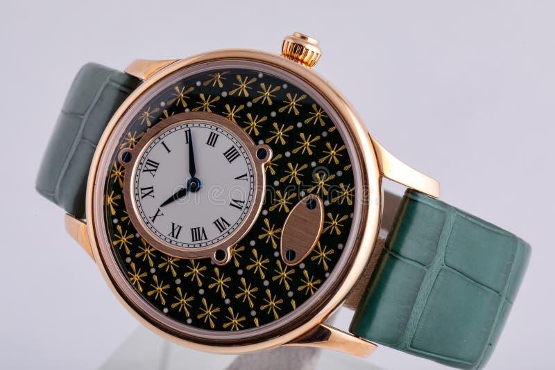 Χρυσό wristwatch με τον άσπρο πίνακα, ο Μαύρος δεξιόστροφα, στο πράσινο λουρί δέρματος που απομονώνεται στο άσπρο υπόβαθρο στοκ εικόνες