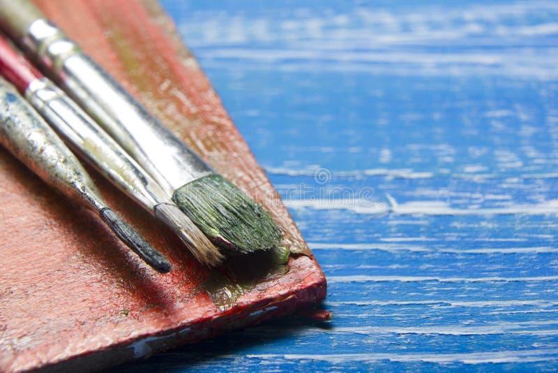 Χρωματίζοντας βούρτσες χρωμάτων παλετών και καλλιτεχνών χρώματος εργαλείων στο αφηρημένο καλλιτεχνικό υπόβαθρο στοκ εικόνα με δικαίωμα ελεύθερης χρήσης