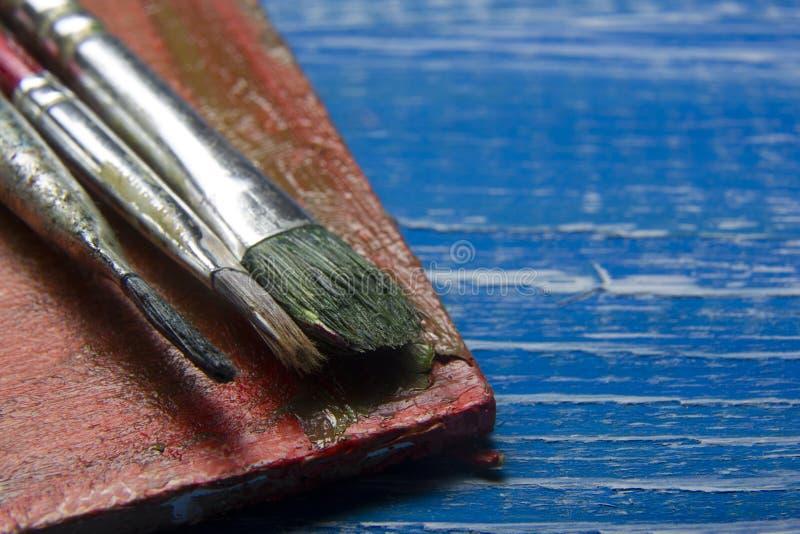 Χρωματίζοντας βούρτσες χρωμάτων παλετών και καλλιτεχνών χρώματος εργαλείων στο αφηρημένο καλλιτεχνικό υπόβαθρο στοκ φωτογραφίες με δικαίωμα ελεύθερης χρήσης