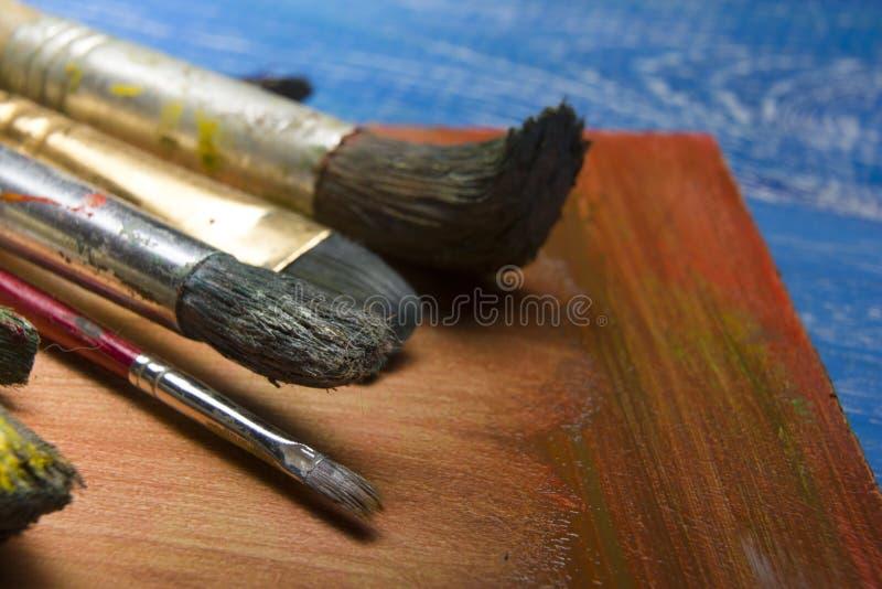 Χρωματίζοντας βούρτσες χρωμάτων παλετών και καλλιτεχνών χρώματος εργαλείων στο αφηρημένο καλλιτεχνικό υπόβαθρο στοκ εικόνες με δικαίωμα ελεύθερης χρήσης