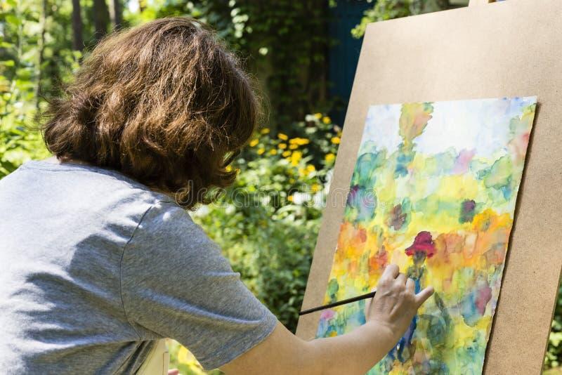 χρωματίζοντας γυναίκα χρωμάτων βουρτσών στοκ φωτογραφία