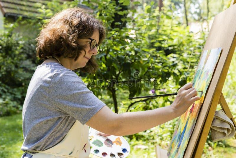 χρωματίζοντας γυναίκα χρωμάτων βουρτσών στοκ φωτογραφίες με δικαίωμα ελεύθερης χρήσης