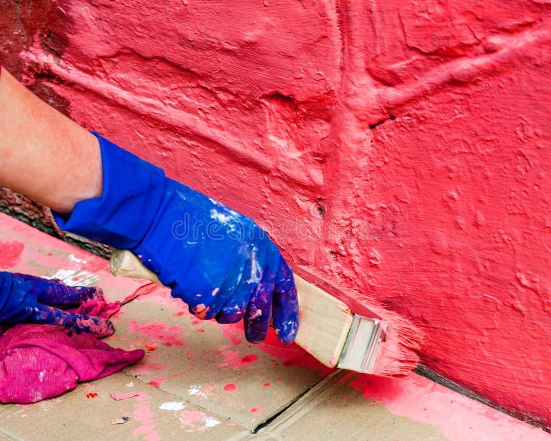 Χρωματίστε τον τοίχο στο κόκκινο με μια μεγάλη ευρεία βούρτσα χρωμάτων στοκ φωτογραφίες με δικαίωμα ελεύθερης χρήσης