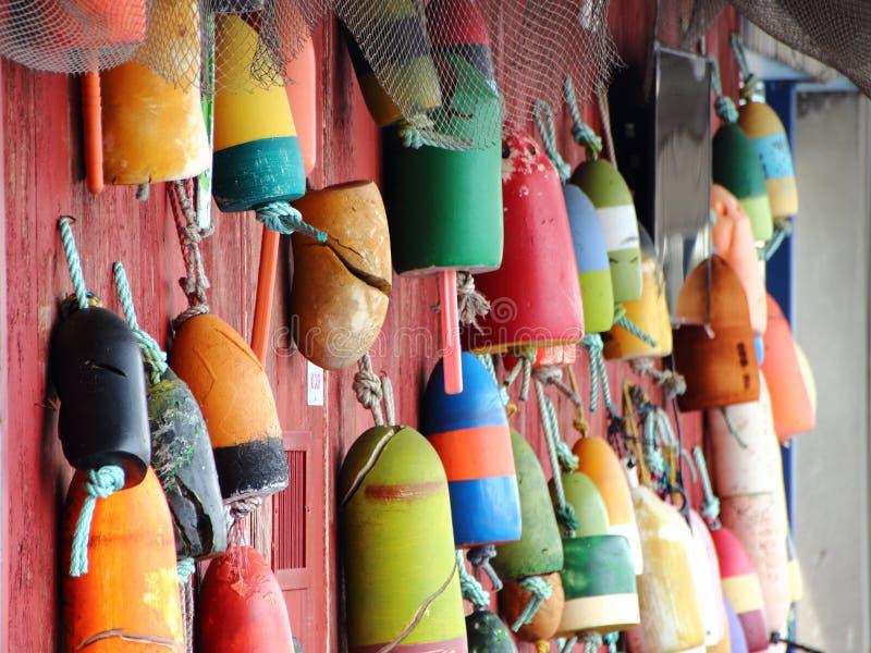 Χρωματισμένα επιπλέοντα σώματα διχτυού του ψαρέματος στον κόκκινο τοίχο στοκ εικόνες με δικαίωμα ελεύθερης χρήσης