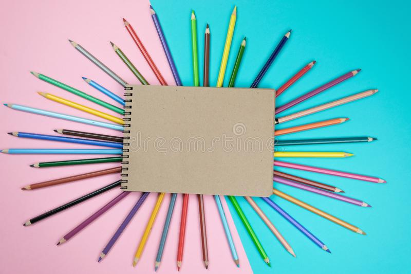 Χρωματισμένα μολύβια, χλεύη σημειωματάριων επάνω για το έργο τέχνης στοκ εικόνες