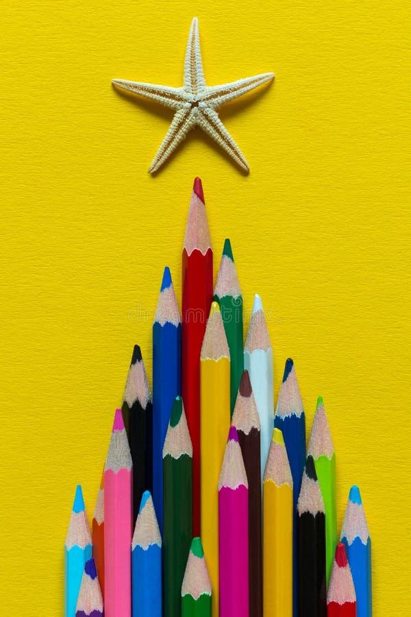 Χρωματισμένα μολύβια που σχεδιάζονται σε μια πυραμίδα Πάνω από τον αστερία μολυβιών Σε ένα κίτρινο υπόβαθρο εγγράφου στοκ φωτογραφία