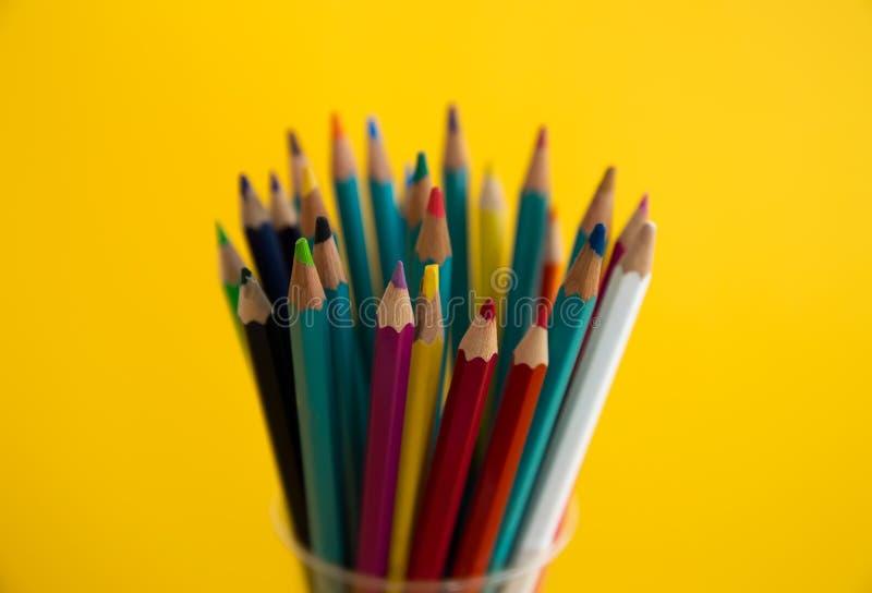Χρωματισμένα ξύλινα μολύβια για το σχέδιο σε μια στάση γυαλιού σε ένα άσπρο υπόβαθρο Πολύχρωμα μολύβια παιδιών για το σχέδιο στοκ εικόνες
