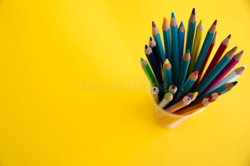 Χρωματισμένα ξύλινα μολύβια για το σχέδιο σε μια στάση γυαλιού σε ένα άσπρο υπόβαθρο Πολύχρωμα μολύβια παιδιών για το σχέδιο στοκ εικόνα με δικαίωμα ελεύθερης χρήσης