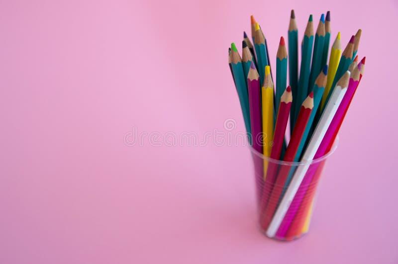 Χρωματισμένα ξύλινα μολύβια για το σχέδιο σε μια στάση γυαλιού σε ένα άσπρο υπόβαθρο Πολύχρωμα μολύβια παιδιών για το σχέδιο στοκ εικόνα
