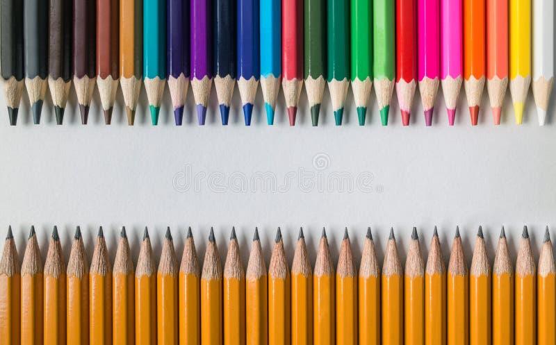 Χρωματισμένα ξύλινα μολύβια μπροστά από τα απλά από γραφίτη μολύβια στον πίνακα που απομονώνεται στοκ εικόνα