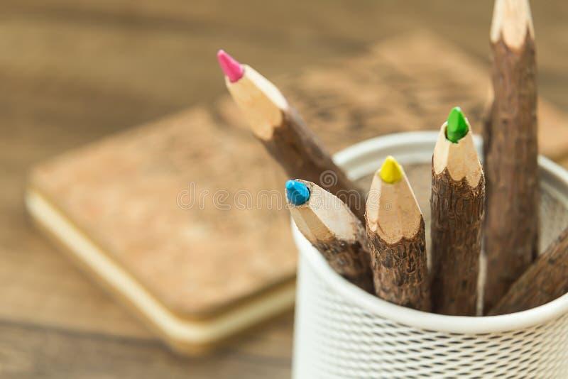 Χρωματισμένα ξύλινα μολύβια στον κάτοχο μολυβιών γραφείων μετάλλων στοκ φωτογραφίες
