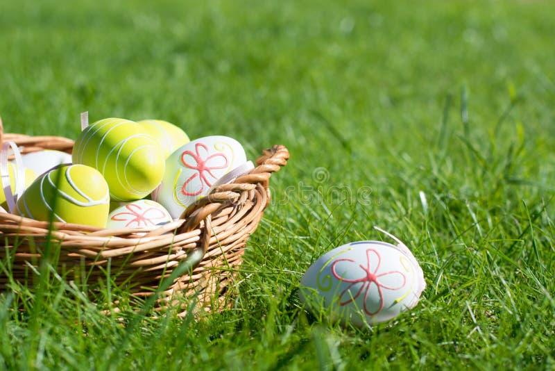 Χρωματισμένα Πάσχα αυγά χρώματος κρητιδογραφιών με την κορδέλλα στην πράσινη χλόη ημέρα ηλιόλουστη κλείστε επάνω Εκλεκτική εστίασ στοκ εικόνες με δικαίωμα ελεύθερης χρήσης
