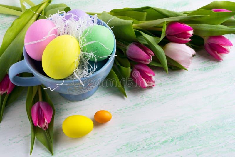 Χρωματισμένα σύμβολο αυγά διακοπών Πάσχας στο μπλε φλυτζάνι και τις ρόδινες τουλίπες β στοκ εικόνες με δικαίωμα ελεύθερης χρήσης