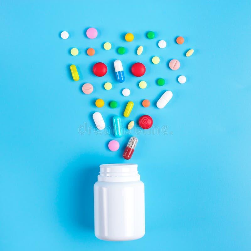 Χρωματισμένα χάπια, ταμπλέτες και άσπρο μπουκάλι στο μπλε υπόβαθρο στοκ εικόνες