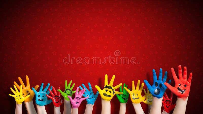 Χρωματισμένα χέρια παιδιών με το smiley μπροστά από το υπόβαθρο Χριστουγέννων στοκ φωτογραφίες