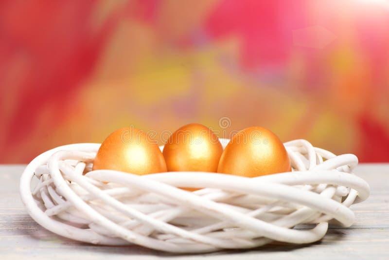 Χρωματισμένα χρυσά αυγά Πάσχας στη φωλιά πουλιών στο ζωηρόχρωμο υπόβαθρο στοκ εικόνες