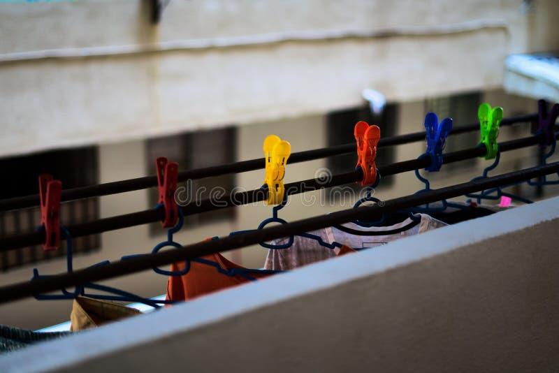 Χρωματισμένα clothespin κρεμώντας ενδύματα εκμετάλλευσης σε έναν φραγμό πολυόροφων κτιρίων στοκ εικόνες