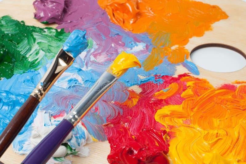Χρωματισμένες ελαιόχρωμα και βούρτσες στην παλέτα στοκ φωτογραφία
