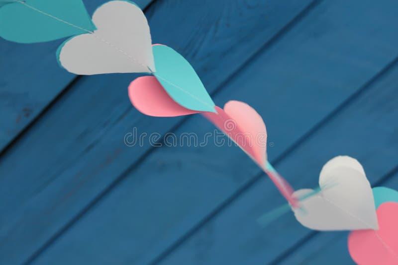 Χρωματισμένες καρδιές εγγράφου σε ένα μπλε υπόβαθρο στοκ εικόνες