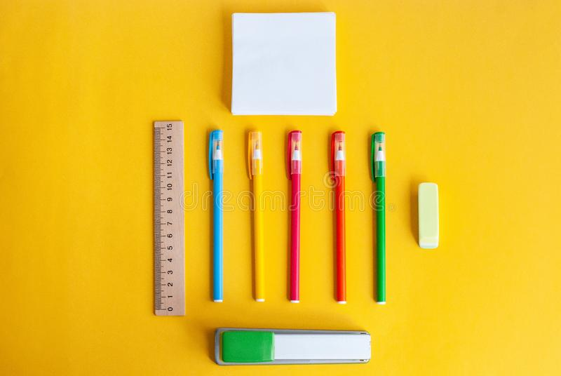 Χρωματισμένες μάνδρες, δίπλα σε έναν ξύλινο κυβερνήτη, γόμα, stapler, έγγραφο για τις σημειώσεις, εξαρτήματα για τη μελέτη σε ένα στοκ εικόνα