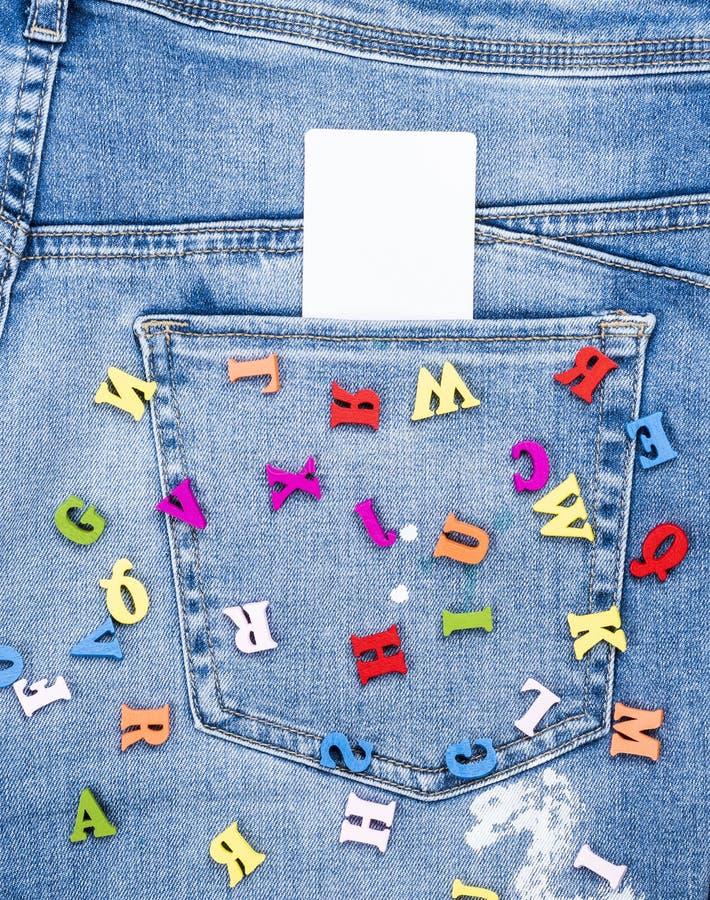 Χρωματισμένες ξύλινες επιστολές που διασκορπίζονται στο τζιν παντελόνι στοκ φωτογραφίες με δικαίωμα ελεύθερης χρήσης