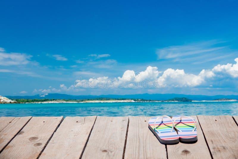 Χρωματισμένες παντόφλες στο ξύλινο πάτωμα κοντά στην παραλία στοκ φωτογραφίες με δικαίωμα ελεύθερης χρήσης