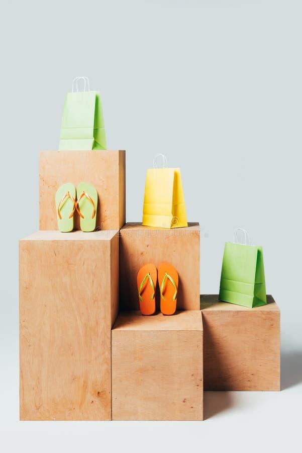 χρωματισμένες τσάντες αγορών και πτώσεις κτυπήματος στις ξύλινες στάσεις, καλοκαίρι στοκ φωτογραφίες με δικαίωμα ελεύθερης χρήσης