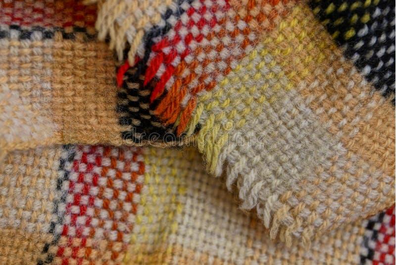 Χρωματισμένη φωτεινή σύσταση με ένα σχέδιο του μάλλινου μαντίλι υφάσματος στοκ φωτογραφία με δικαίωμα ελεύθερης χρήσης