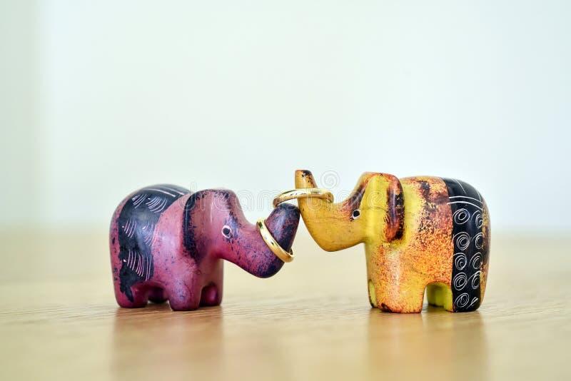 Χρωματισμένοι ελέφαντες παιχνιδιών που συνδέονται με τα γαμήλια δαχτυλίδια ως σύμβολο της οικογενειακής ευτυχίας στοκ φωτογραφία με δικαίωμα ελεύθερης χρήσης