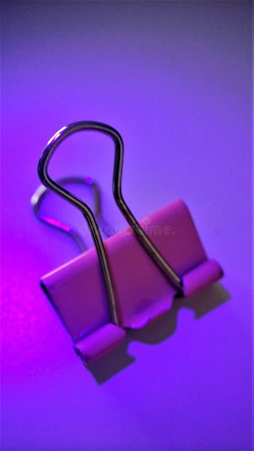 Χρωματισμένοι συνδετήρες εγγράφου κάτω από τις ακτίνες υπεριώδης μακρο κινηματογράφηση σε πρώτο πλάνο για το υπόβαθρο στοκ φωτογραφία με δικαίωμα ελεύθερης χρήσης