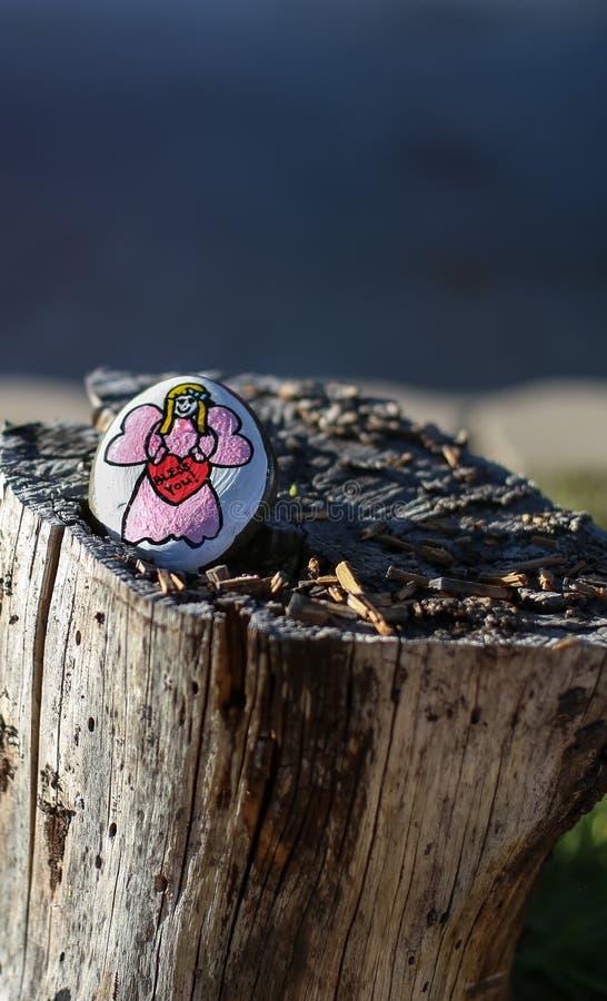 Χρωματισμένος βράχος με τον άγγελο cartoonish από τον ουρανό στοκ φωτογραφία
