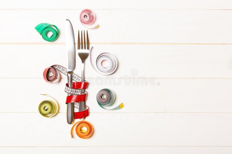 Χρωματισμένος οι ταινίες, το δίκρανο και το μαχαίρι μέτρου στο ξύλινο υπόβαθρο Τοπ άποψη της έννοιας weightloss με το κενό διάστη στοκ εικόνες