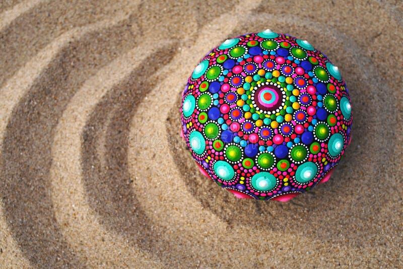 χρωματισμένος χέρι βράχος mandala στην άμμο στοκ φωτογραφία