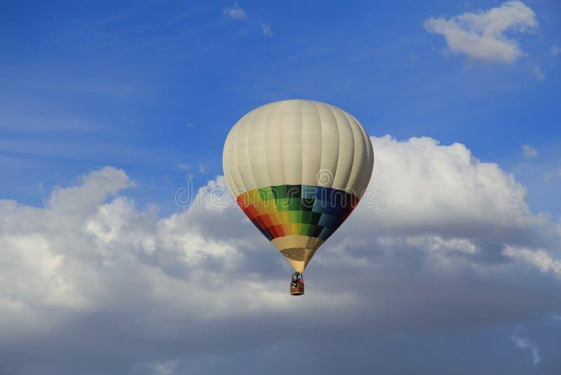 χρωματισμένο αεροστατικό μπαλόνι που πετά σε έναν μπλε ουρανό με τα άσπρα σύννεφα στοκ εικόνες