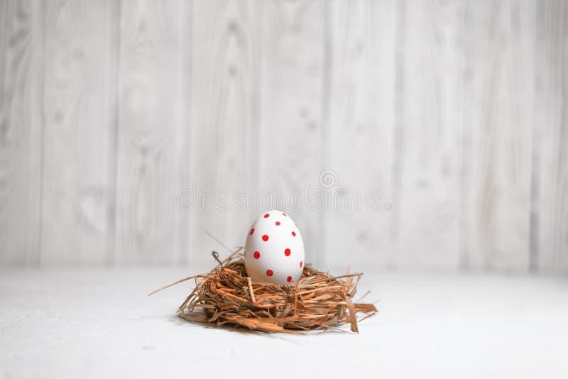Χρωματισμένο αυγό Πάσχας σε μια φωλιά σανού σε ένα ελαφρύ υπόβαθρο στοκ φωτογραφίες με δικαίωμα ελεύθερης χρήσης