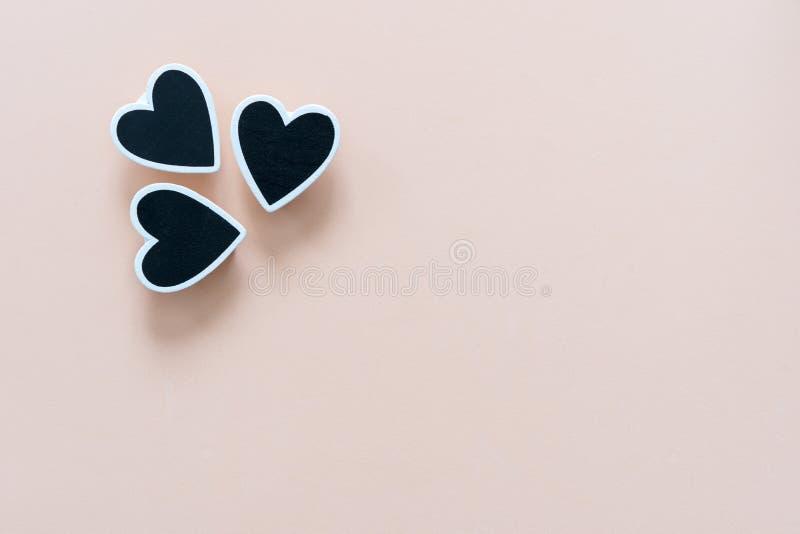 Χρωματισμένο κρέμα υπόβαθρο, με τρεις μαύρες καρδιές σε ένα τέλος Έννοια αγάπης, για την ημέρα του βαλεντίνου, ημέρα της μητέρας, στοκ φωτογραφίες