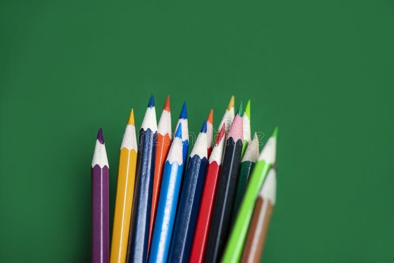 Χρωματισμένο μολύβι που τίθεται στο πράσινο υπόβαθρο πίσω στο σχολείο και την έννοια εκπαίδευσης/κραγιόνια ζωηρόχρωμα στοκ εικόνες