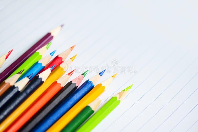 Χρωματισμένο μολύβι που τίθεται στο σημειωματάριο της Λευκής Βίβλου πίσω στο σχολείο και την έννοια εκπαίδευσης/κραγιόνια ζωηρόχρ στοκ εικόνα