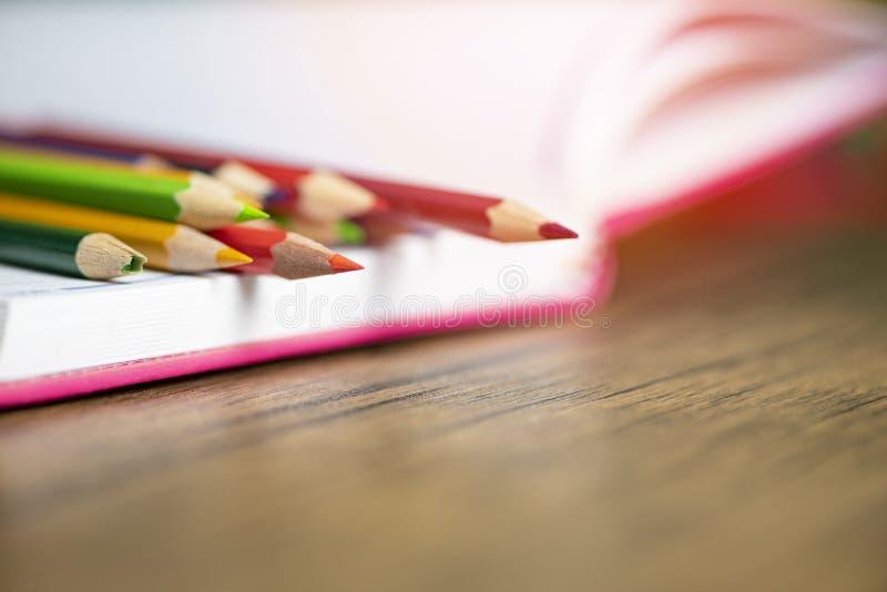 Χρωματισμένο μολύβι που τίθεται στο σημειωματάριο της Λευκής Βίβλου πίσω στο σχολείο και την έννοια εκπαίδευσης/κραγιόνια ζωηρόχρ στοκ εικόνα με δικαίωμα ελεύθερης χρήσης