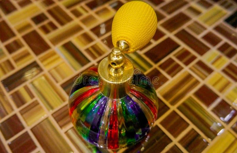 Χρωματισμένο μπουκάλι ψεκασμού γυαλιού στην κεραμωμένη επιφάνεια στοκ φωτογραφία