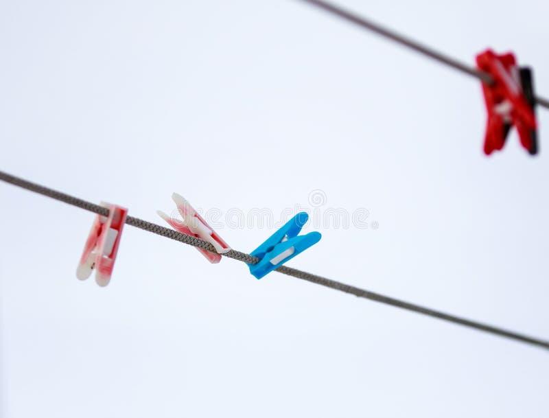 Χρωματισμένο πλαστικό clothespins που κρεμά στη σκοινί για άπλωμα επάνω στοκ φωτογραφίες