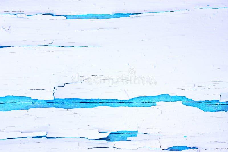 Χρωματισμένο τραχύ ξύλινο υπόβαθρο, παλαιός τοίχος με το ραγισμένο λευκό χρωμάτων στο μπλε σκηνικό στοκ εικόνα