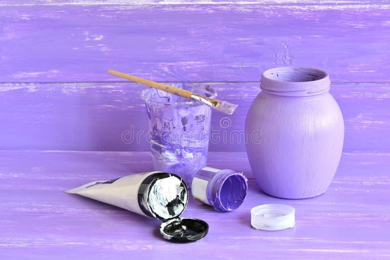 Χρωματισμένο χέρι μπουκάλι Πώς να διακοσμήσει το συνηθισμένο βάζο γυαλιού Ιώδες και άσπρο ακρυλικό χρώμα, βούρτσα, που τίθεται γι στοκ εικόνα