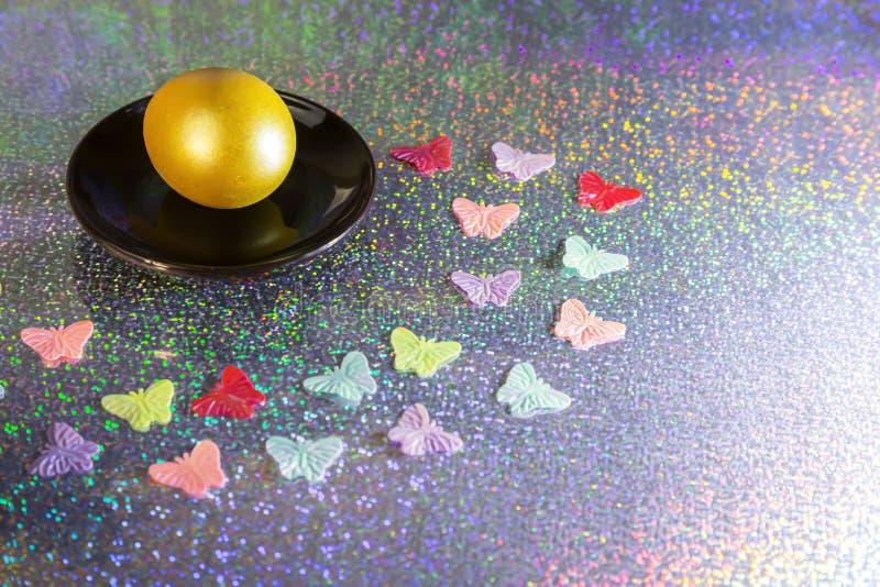 r Χρωματισμένο χρυσό κίτρινο αυγό σε ένα μαύρο πιάτο σε ένα αφηρημένο μπλε ολογραφικό λαμπρό υπόβαθρο στοκ φωτογραφίες με δικαίωμα ελεύθερης χρήσης