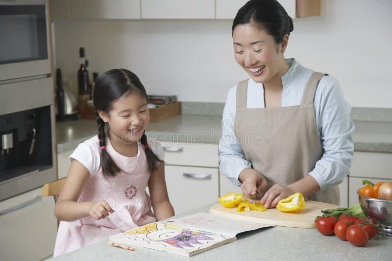 Χρωματισμός κορών και τέμνον πιπέρι κουδουνιών μητέρων στην κουζίνα στοκ εικόνες