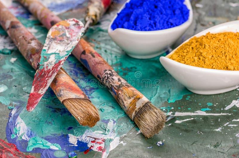 Χρωστικές ουσίες βουρτσών, spatula και χρώματος σε μια ξύλινη παλέτα στοκ φωτογραφία